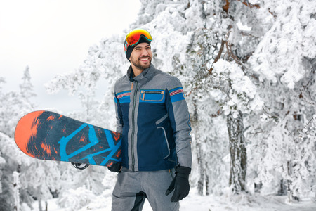 Smiling young snowboarder holding board for snowboarding