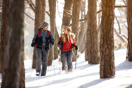 Happy female and male hiker walking in forest
