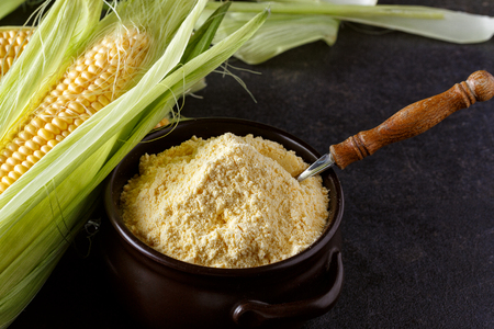 corn grits in bowl and fresh corn on black table background Stock Photo