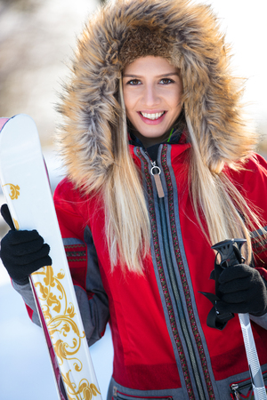 Young female skier with skis and poles