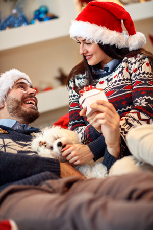 Christmas, holidays and people concept - happy couple in Santa hats with gift box at home