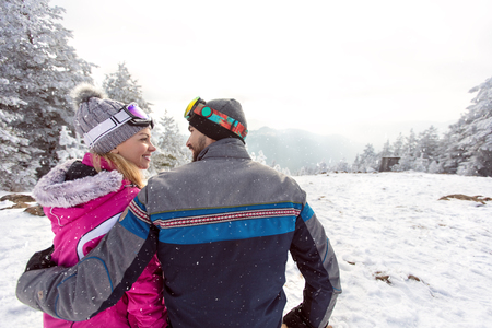 Woman and man in love on winter holiday together on ski terrain, back view