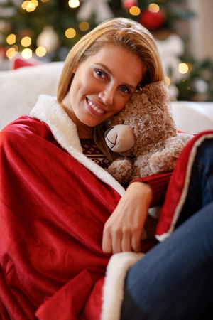 Young woman hugs teddy bear in Christmas eve