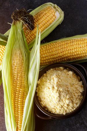 Fresh Corn and corn grits in bowl on black table background Reklamní fotografie