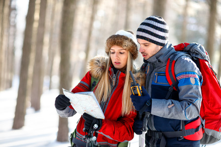 Mountaineers couple looking for path on map in wood on winter Banque d'images
