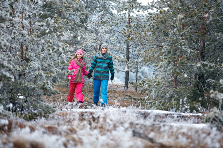 Boy and girl walking together in snowy mountain Banque d'images