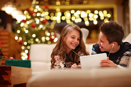 Happy children together listen music with earphones from tablet in Christmas eve