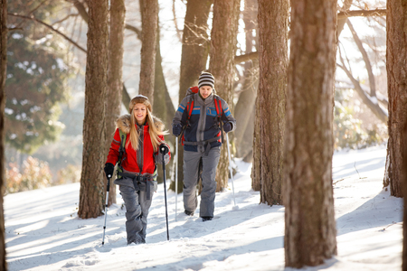 Young male and female hiking in winter forest