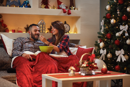Girl feeding boyfriend with popcorn in bed while watching movie for Chrismas eve Stock Photo