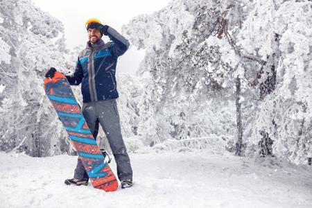 Jeune beau snowboarder mâle sur la montagne Banque d'images - 88960577
