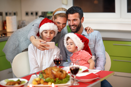 Family with children making Christmas selfie together at the table with food