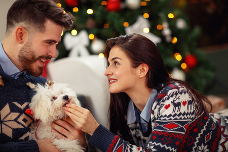 Happy woman with husband at home with cute dog celebrating Christmas eve