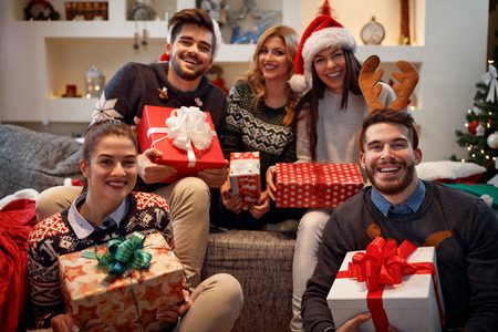 Cheerful friends holding colorful boxes with Christmas gifts Banque d'images