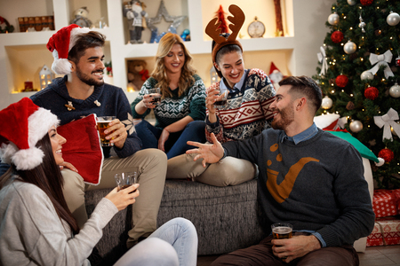Group of happy friends having fun together in Christmas eve