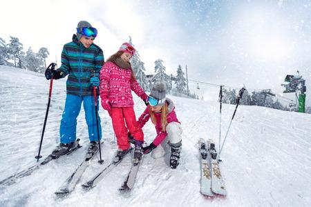 Skiing, winter fun-Mother preparing for skiing happy kids