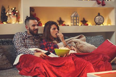 Paar dat thuis popkorrels eet terwijl het letten van op film op TV Stockfoto - 88960893