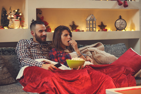 Couple at home eating pop corns while watching movie on tv