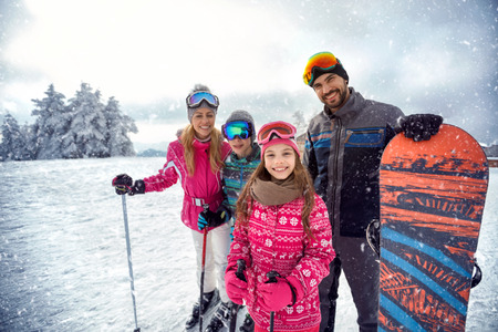 smiling family enjoying winter sports and vacation on snow in mountains 免版税图像 - 88960898