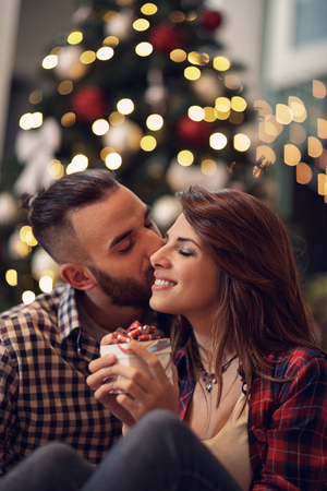 Young couple in love kisses at Christmas eve while holding gift in hands