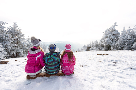 Group of tree children sitting on ski terrain, back view Stock fotó