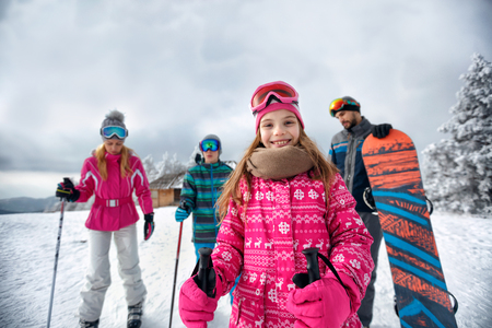young smiling girl with family on ski slope on vacation in mountain together Stock Photo