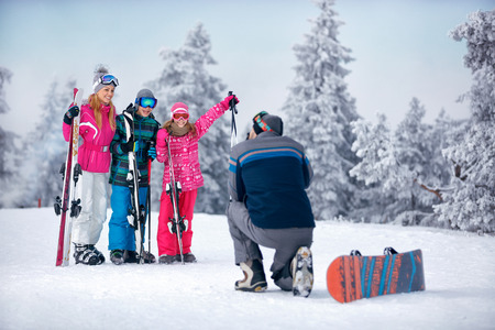 father taking picture of happy family standing in snow on the mountain Banque d'images