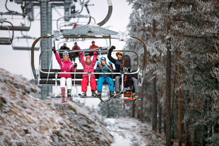 Ski lift transport family skiers and snowboarders at holiday in snowy mountain