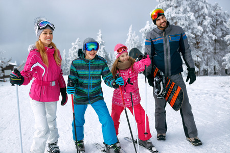 smiling happy family with ski and snowboard on ski holiday in mountains