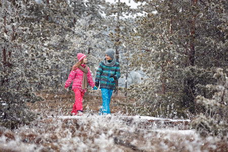 little happy boy and girl walking in snowy mountain