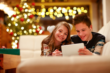 happy boy and girl with headphones lying and using a tablet for Christmas