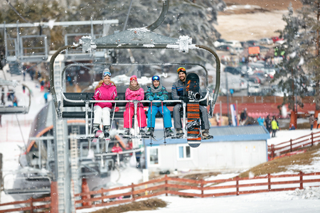 Young happy family on ski lift
