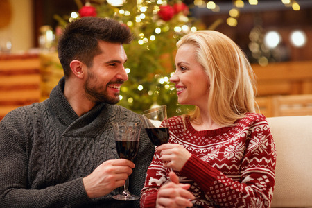 Loving couple celebrating Christmas toasting with glasses of red wine Banque d'images