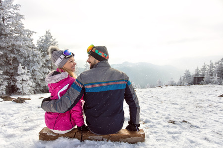 Happy couple in love sitting on ski terrain at winter holiday Stock fotó