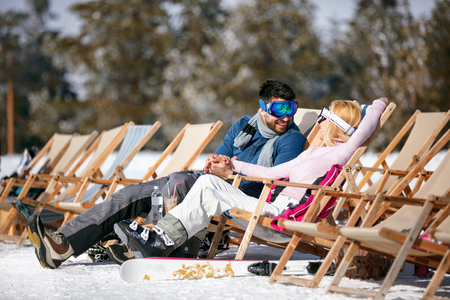 happy couple in love at mountains in winter laughing and relax in sunbed
