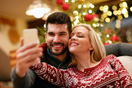 smiling romantic couple taking selfie picture with smartphone at home