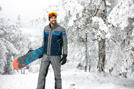 Handsome sportsman with board in snowy nature