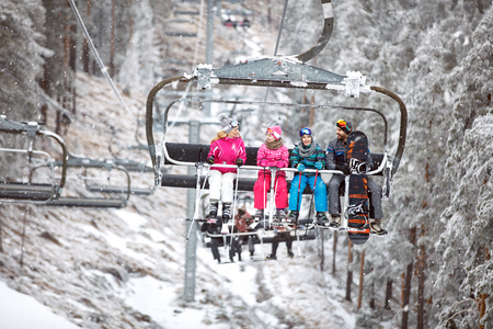 Family together in ski chair going to ski terrain on mountainside