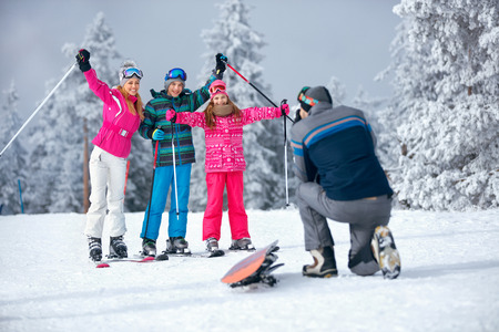 father taking picture of happy family on ski holiday in mountains