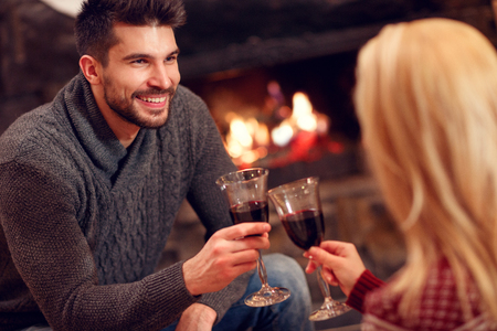 Young romantic couple sitting on floor at burning fireplace and drink wine Banque d'images