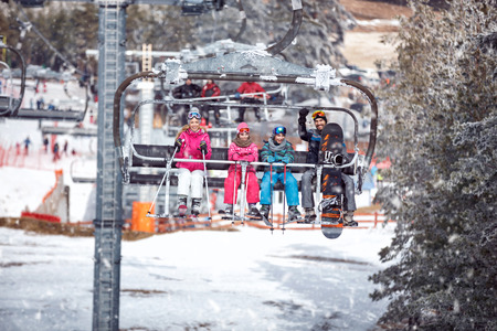 Skiers at the ski resort on a background of ski-lifts, forests, mountains at the sunny day. Ski season and winter sports concept