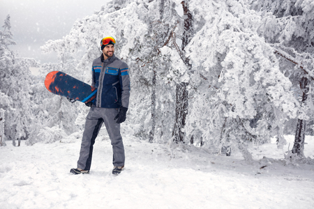 young smiling snowboarder with snowboard on winter holiday in the mountain Banque d'images