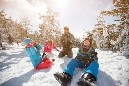 Family with children having fun on snow in mountain at winter Banque d'images