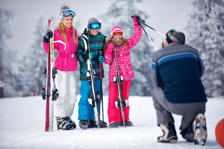Ski, snow sun and fun - father taking picture of happy family on snow