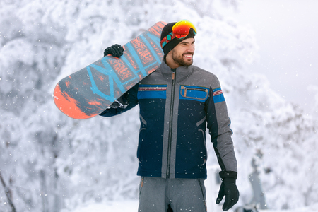 Young snowboarder holding board on ski terrain