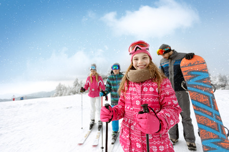 Smiling girl with family on ski terrain ready for skiing Imagens