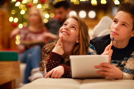 cute boy and girl lying and writes letter to Santa Claus for Christmas
