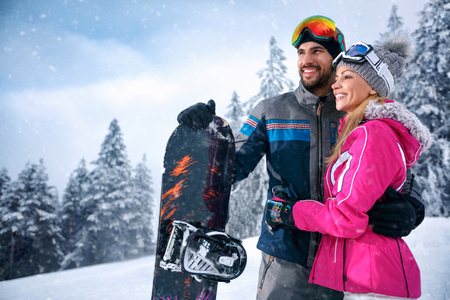 love smiling couple enjoying on winter vacation together on the snow mountain