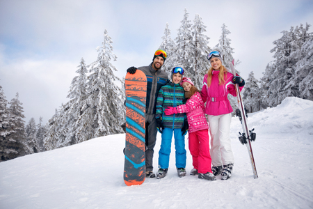 Happy family enjoying in winter vacations together in mountains Zdjęcie Seryjne - 90110780