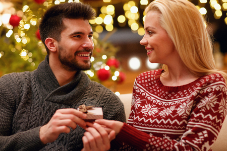 romantic man suprise woman with gift for Christmas holiday