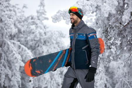 Homme avec masque de ski tenant son snowboard, sport extrême et vacances d'hiver sur la montagne Banque d'images - 90110826